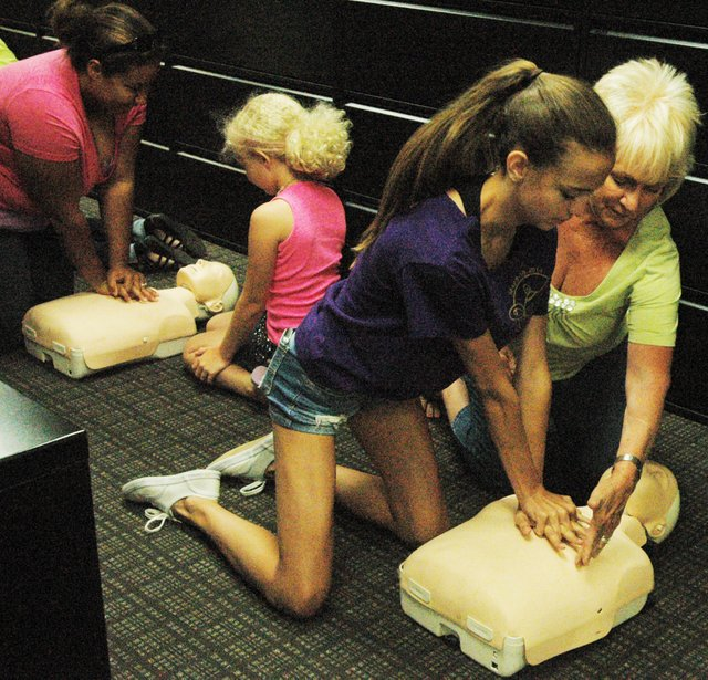 Jan Hewitt and her granddaughter, Grace, practice compression-only CPR under the direction of the Shawnee Fire Department.