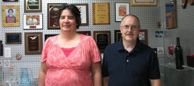 Laura and James Smith stand in the show room of Basehor Awards and Trophies.