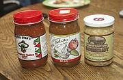 A number of products on the shelves of local grocery stores are processed at the commercial kitchen at Antiques on the Prairie, including the two salsas and sauerkraut show here.