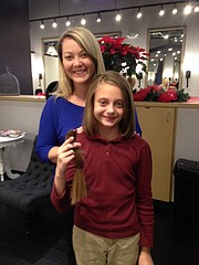Jeydan Umberger, 9, stands with Heather Kendall, owner of Bella Dea Salon and Boutique, after having 10-inches of her hair cut for the Locks of Love charity.