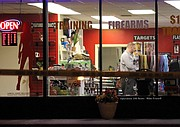 A Johnson County Sheriff's Office crime scene technician documents evidence inside the store around 3 a.m. Saturday. Bullet holes and evidence markers can be seen in the front window.