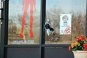 Evidence markers can be seen near bullet holes in the broken front glass of the shop.