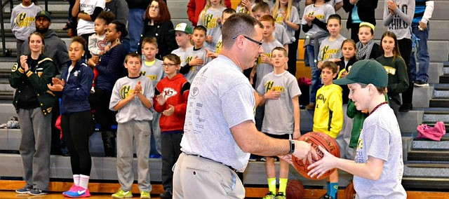 Basehor-Linwood boys basketball coach Mike McBride presents fifth grader Hayden Hand with an autographed basketball.
