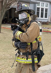 A Shawnee firefighter carries Harley, one of the family's two cats from the house. Harley was inside the burning home for at least 90 minutes.
