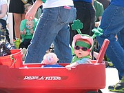 Emily Merrion, 7 months, of Lenexa is pulled in her Radio Flyer in the Shawnee St. Patrick's Day Parade on Sunday.