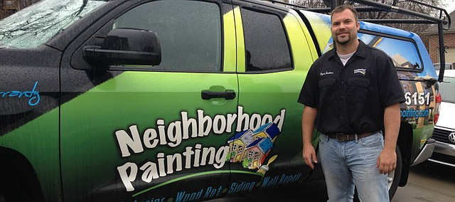 Ryan Toelkes, owner of Neighborhood Painting, LLC., stands with one of his company trucks.