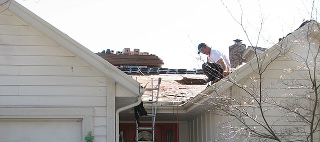 Roofers work to replace the roof on Elizabeth Pfiffer's house in Shawnee.