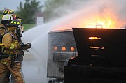Teams running to fire hoses approach a blazing prop dumpster during training Wednesday for firefighters with the Baldwin City Fire Department and those of Palmyra and Willow Springs Township. The props for the training set up the BESPC were provided by the Kansas University Fire and Rescue Training Institute.