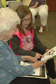 Ava Rushing follows along with her finger as she reads to Mary Whitney (left).