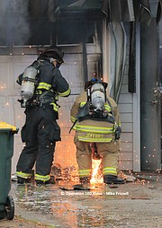 Overland Park firefighters use a saw to remove the home's garage doors.
