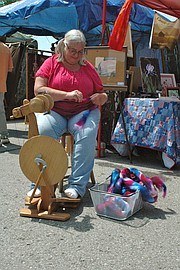 Beth Donovan of Easton spins some fiber on her aura wheel, a spinning wheel constructed in New Zealand, at the 2014 Festival of the Arts in Downtown Bonner Springs.