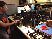 A designer works with the 3-D printer in the Device Shop's lab.