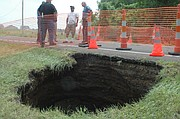 Lloyd Martley, Basehor police chief and city administrator, far right, and other public works employees discuss appropriate measures to address the sink holes that developed on Parallel Road just east of 159th Street. The road may be closed for about three weeks.