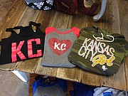 "Sideline Chic carries sports fan apparel for women, including several officially licensed collegiate items along with the ""Kansas City"" shirts themed for Kansas City's professional sports teams, like the Kansas City Chiefs-themed shirts above."
