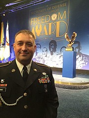 Army Reservist Sgt. 1st Class and Shawnee firefighter Douglas Simms stands in front of the the Freedom Award at the Pentagon last week. Simms nominated Shawnee for the award earlier this year.