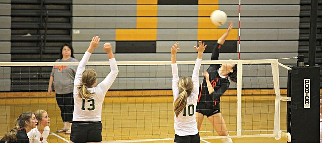 Bonner Springs' Natalie Klotz (18) goes for a kill as Basehor-Linwood's Ava Seaton (10) and Katie Yankowich (13) attempt to block.