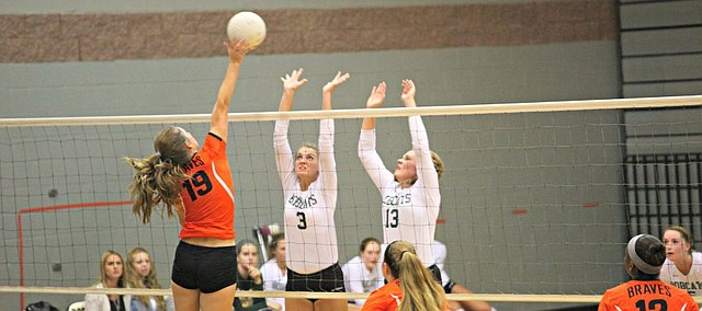Bonner Springs' Paige Krone (19) goes for a kill as Basehor-Linwood's Madi Osterhaus (3) and Katie Yankovich (13) attempt to block.