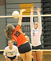 Bonner Springs' Paige Krone (19) goes for a kill as Basehor-Linwood's Courtney Norris attempts to block.