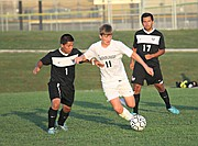 Basehor-Linwood midfielder Jonathan Harms tires to fend off a Bishop Ward player.