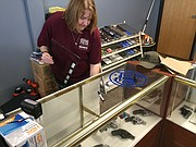 Becky Bieker works on one of her display cases at the new She's A Pistol location at 6487 Quivira Road.
