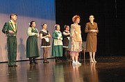 "At right, Annie, played by Heidi Rodgers, and Grace Farrell, played by Lillian Kaus, sing ""I think I'm gonna like it here,"" along with the staff of the Warbucks mansion during the presentation for elementary school students Monday."