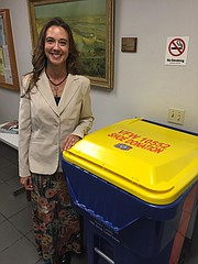 Mayor Michelle Distler stands next to a Tony Lang 1,000 Shoes Campaign collection bin at City Hall.