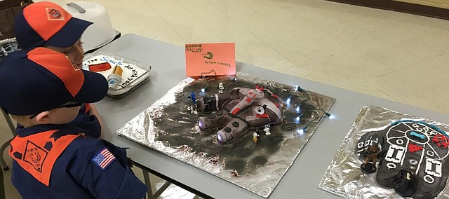 A couple Cub Scouts look at the many entries in the Star Wars category of the Cake Bake Competition.