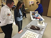 Mayor Michelle Distler and Fire Chief John Mattox look at the many cakes entered in the Star Wars category.