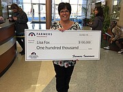 Lisa Fox, a longtime kindergarten teacher at St. Joseph Catholic School, holds up the oversized check she received Wednesday along with the announcement that her proposal had won the school a $100,000 from Farmers Insurance's Thank America's Teachers Dream Big Teacher Challenge. The funding will go toward providing one iPad for every student.
