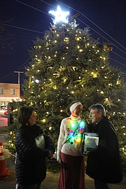 Mayor Michelle Distler, wearing the colorful lights, stands with Kriste Everett and Robbie Marts who helped her light this year's Mayor's Christmas Tree. Everett was honored with a Good Neighbor Award and Marts was presented with a certificate and key to the city.