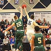 Mill Valley's Clayton Holmberg (35) and Basehor-Linwood's Nick Fisher (22) go for the opening tip.
