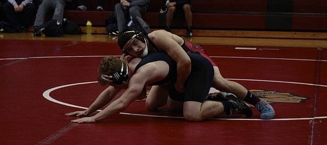 Shawnee Mission North senior Cesar Salgado keeps control following a takedown against Blue Valley North's Danny Pursley during SM North's dual Thursday against the Mustangs. Salgado went on to win by fall in the second period, but SMN fell to the Mustangs, 58-18.