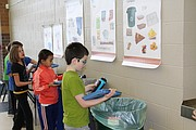 Students carefully discard their lunch leftovers in bins according to the charts posted on the way for recycling, composting and trash Friday at Ray Marsh Elementary.