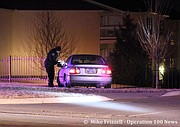 A Shawnee Police officer gathers information from the crashed suspect vehicle at the entrance to Prairie Lakes Apartments, 6800 block of Lackman Road.