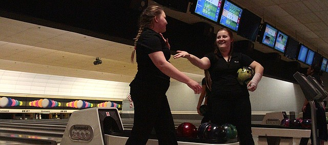 Shawnee Mission Northwest's Katy Doleshal (left) high-fives teammates Alaina Burris (right) after rolling a strike Thursday at the Sunflower League Championships at Olathe Lanes East. Burris and Doleshal finished first and second respectively to lead the SM Northwest girls bowling team to a second-place finish.