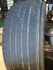 A tire that shows uneven tire ware and tread depth.