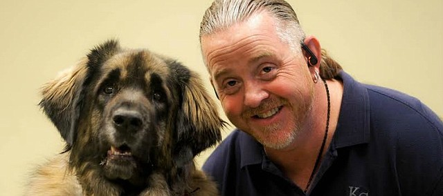 Mike Deathe, owner of KISS Dog Training in Shawnee, poses with his Leonberger named Lexi.