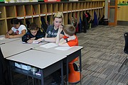 Kelsey Porter, third grade teacher (second from right), works with (from left) Valeria Cazares, Jeremy Hendrickson and Jake Rigsby on math worksheets as they sit on the new Hokki chairs near their cubbies, something they didn't have space for in the old building.