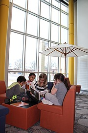 Shawanoe kindergartners (from left) Emanuel Anaya Sanchez, Sharifa Arian, Tagan Barnett and Lauren Bennett read a book in the library at the new Shawanoe building, which students and staff moved into Tuesday. The former Shawanoe building can be seen through the library window.