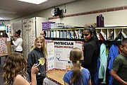 Janmeet Singh, far right, discusses requirements for a physician with younger students at Broken Arrow's sixth grade career fair.