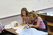 Ella Hammond (left) and Harlow Medved pretend to be veterinarians during play time of the Jump Start program Friday at Bluejacket-Flint Elementary School. Learning to role play is an important social aspect for the future kindergartners.