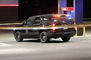 A Lenexa Police Department vehicle roped off by crime scene tape in the QuikTrip parking lot following an officer involved shooting.