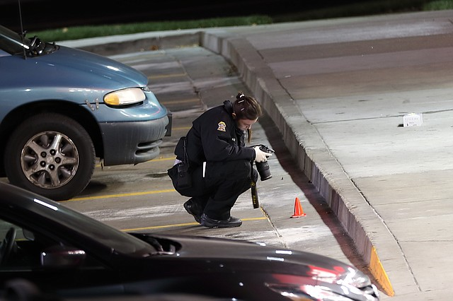 A Johnson County Sheriff's Office Crime Scene Technician photographs evidence in front of the QuikTrip following an officer involved shooting.