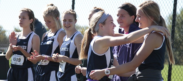 St. James Academy senior Carlie Yunger reaches in to hug teammate Gabrielle Boucher while accepting her medal for fourth place at Saturday's Class 5A regional meet at Johnson County Community College as Thunder freshmen and fellow medalists Sarah Murrow, Katherine Moore and Hannah Robinson look on. All five of the Thunder runners placed in the top 10 to clinch a regional title for St. James.