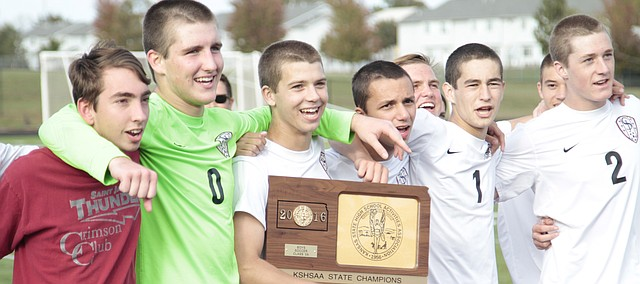 St. James Academy senior Brady Manning holds the Class 5A state soccer championship plaque while being surrounded by fellow seniors Jake Dunsmore (0), Alessandro DeBrevi (to the right of Manning), Luke Schaefer (1) and Jack DuBois (2). Manning, Schaefer and DuBois — the three St. James captains — scored a goal apiece to lead the Thunder to a 3-1 win over Blue Valley Southwest Saturday at Emporia High School.