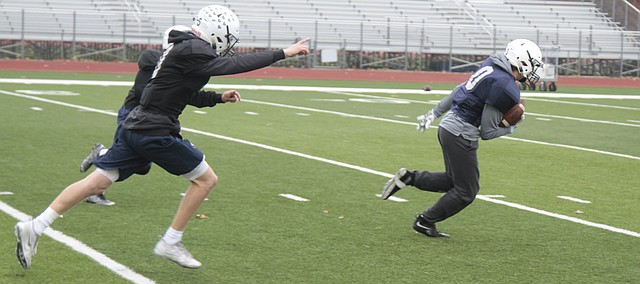 Mill Valley sophomore safety Tanner Moore runs back an interception while fellow defensive back Cole Ivey raises up his arm Wednesday at the Jaguars' practice. The Jaguars will take on Goddard at 1 p.m. Saturday in the Class 5A state title game at Pittsburg State's Carnie Smith Stadium.