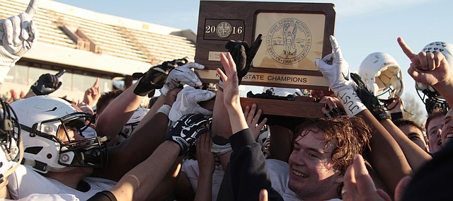 The Mill Valley football team hoists the Class 5A state championship plaque after defeating Goddard, 35-34, Saturday in double overtime at Pitt State's Carnie Smith Stadium. It was the second straight state title for the Jaguars.