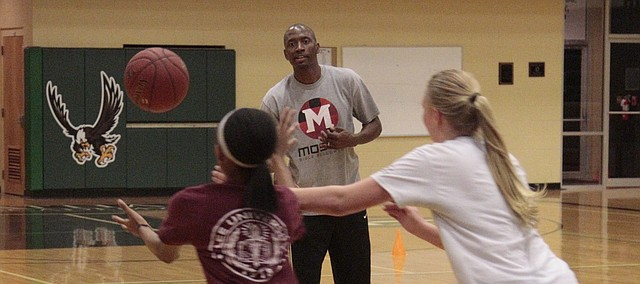 Maranatha Christian Academy girls basketball coach Reggie Hines passes the ball to his daughter, Phoebe Hines (left), while Alyssa Buettner (right) tries to make a steal in the Eagles' practice on Nov. 14.