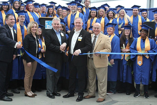 Shawnee City Councilman Jim Neighbor, front right, poses with Walmart executives and the first graduating class of the training academy, as the celebratory ribbon is cut.