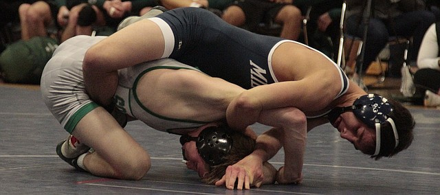 Mill Valley senior Dylan Gowin wraps himself around Blue Valley Southwest sophomore Joseph Dennison on Thursday in the 120-pound match of the Jaguars' dual against the Timberwolves. Gowin won by fall in the second period, but the Timberwolves went on to win the dual, 34-33.
